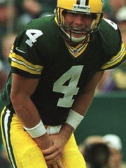 Green Bay Packers quarterback Brett Favre holds his hand after injuring it during the third quarter.