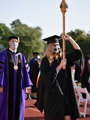 Andrea Picklesimer, Assistant Professor of Nursing Education, carries the university mace as the commencement ceremony began on Saturday morning at the Graves Family Sports Complex.
