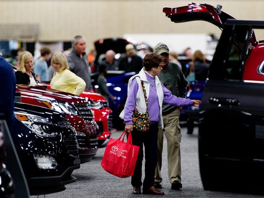 Visitors browse an aisle of automobiles at the annual