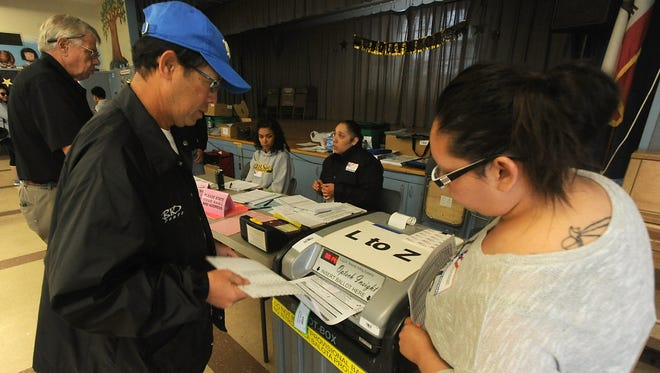A voter is seen placing his ballot in a ballot box at Tierra Vista School in Oxnard during the 2016 elections. The council is in the process of possibly adopting district elections  for 2018.