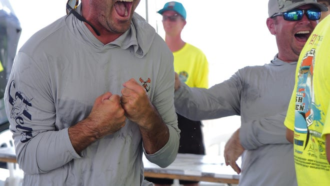 Crew members from Zach Crabtree's boat, Vamoose, react in excitement when the 50.53-pound kingfish has its weight is displayed on the screen during the Greater Jacksonville Kingfish Tournament.
