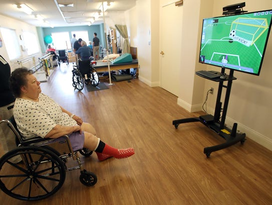 Patty Selaya, 69, kicks the soccer ball on the screen