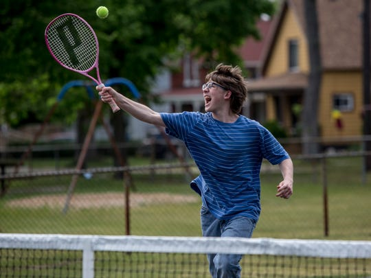 Nathan Cotter, 17, of Port Huron, takes a swing while playing tennis with friends Friday, May 27, 2016 at Lincoln Park in Port Huron.