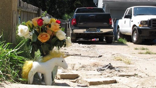 A makeshift memorial rests on the sidewalk Monday, Aug. 3, 2015, at the location where Memphis, Tenn., Police Officer Sean Bolton was fatally shot. Tremaine Wilbourn, the ex-con accused of killing the Memphis Police Officer turned himself into federal authorities Monday after a two-day manhunt. (AP Photo/Adrian Sainz)