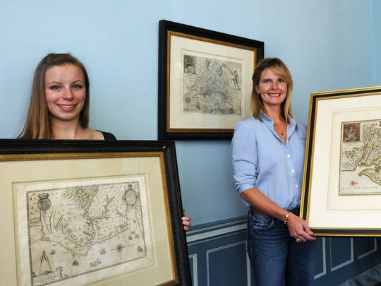 Jenny Barker, executive director of The Eastern Shore of Virgina Historical Society, is joined by Alexis Jason-Matthews and Taylor Rash, of Arader Galleries of New York City, in displaying several of the earliest maps of the Eastern Shore, including a map of 1590, at left.