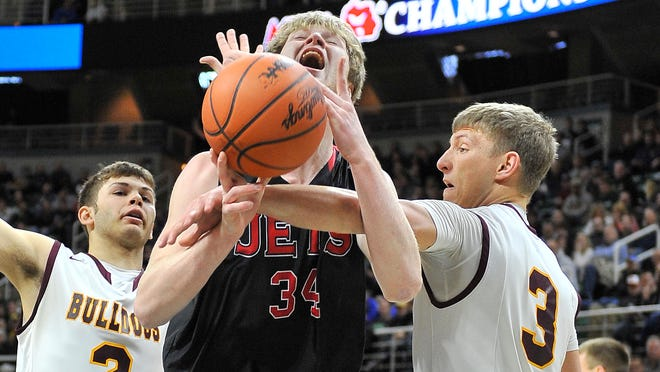 North Central's Caleb Martin is fouled by Morenci's Torin Merillat with Bladen Mellon defending in the first quarter.