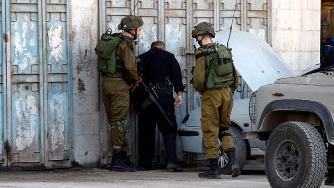 Members of the Israeli armed forces check the site where two Palestinians were shot and killed after reportedly stabbing and wounding two Israeli soldiers near Nablus, West Bank on Sunday.