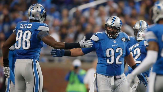 Devin Taylor, left, and Haloti Ngata of the Lions celebrate a tackle against the Vikings at Ford Field.
