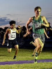 Joe Curtsinger of Bishop Brossart and Sam Gabbard of South Dearborn power across the finish line in the DII/DIII run of the Moeller Primetime Cross Country Invitational.