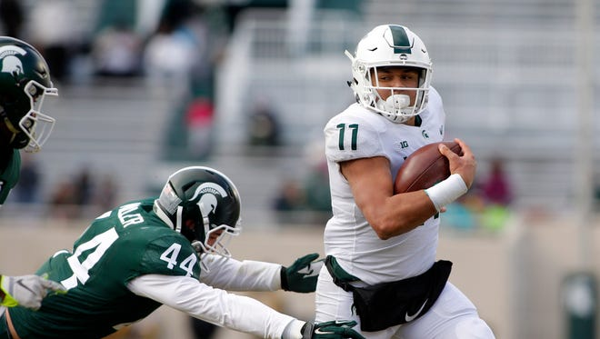 Michigan State running back Connor Heyward rushes past linebacker Grayson Miller during the spring game Saturday, April 7, 2018, in East Lansing.