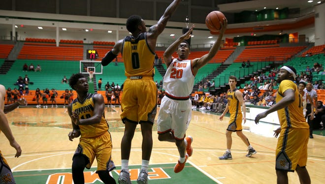FAMU's Brendon Myles makes a layup over Kennesaw State's Kendrick Ray during their game at the Al Lawson Center on Wednesday, Nov. 30, 2016.