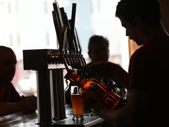 In this file photo, Patrick Meehan pours a growler