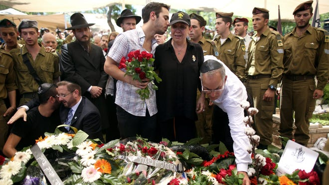 Sgt. Max Steinberg's parents place flowers on his grave during his funeral at the Mount Herzl cemetery in Jerusalem. Tens of thousands of people attended.