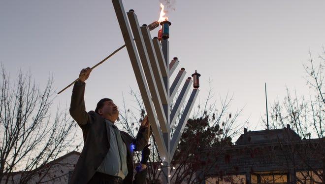 Las Cruces Mayor Ken Miyagishima and Mesilla Mayor Nora Barraza light the center candle on the 9 foot Menorah.