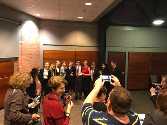 Parents take photos of the Ray High School mock trial team after winning the Region 2 contest Saturday.