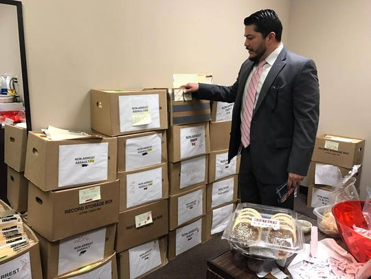 Mark Gonzalez looks through boxes of years-old pending