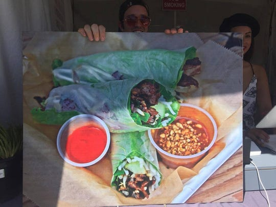 A worker at Xoia Vietnamese holds up a picture of their spring rolls.