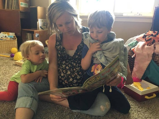 Katie Banta, 31, of Chili reads with her children. The mom of two said she no longer worries about household clutter. Instead, she focuses on keeping her kitchen and laundry clean.