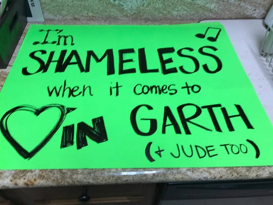 Jamie Guillot quotes Garth Brooks in her sign for his opening night concert in Lafayette June 23. Brooks sang to her and her fiance the week before their wedding.