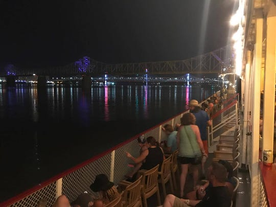 Festival goers catch the river breeze on the upper deck while the Preservation Hall Jazz Band wails beneath them on the Belle of Louisville.