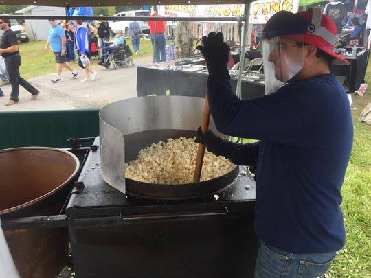 Dan Ferrirra of Kettle Corn Hut stirs a batch. The