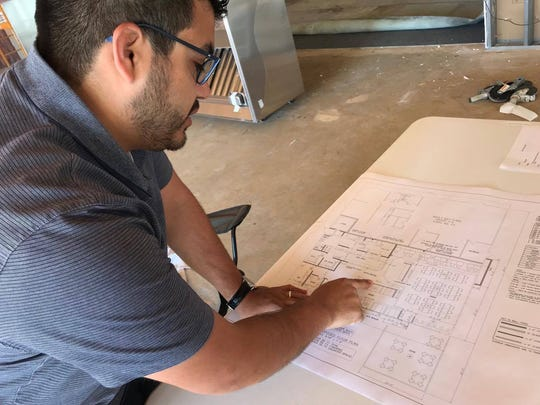 Luis Melendez goes over blueprints for he and his sister's new restaurant, La Taqueria.
