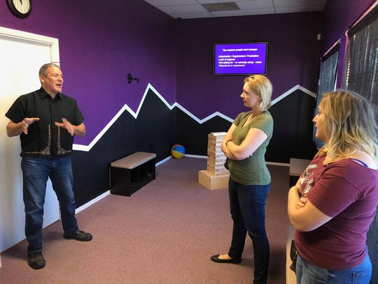 Lost Cruces Escape Room Managing Director Griffn Allen, left, explains the escape room to Pulse freelancer Cassie McClure, middle, and her friend Jennifer Byers, right.
