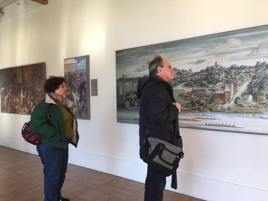 Eileen Gruben and Paul Gruben look at a painting on