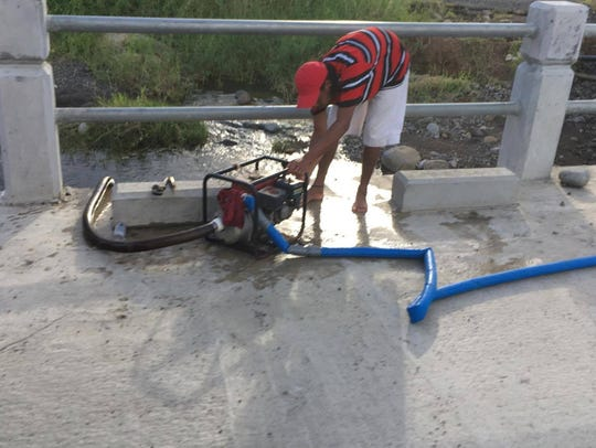 A Dominican pumps water from a river two months after