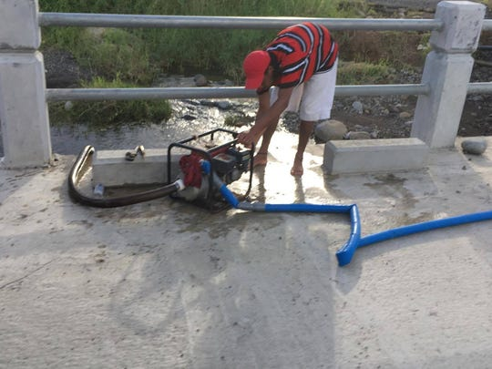 A Dominican pumps water from a river two months after Hurricane Maria. The storm ravaged the country and made access to clean drinking water problematic.