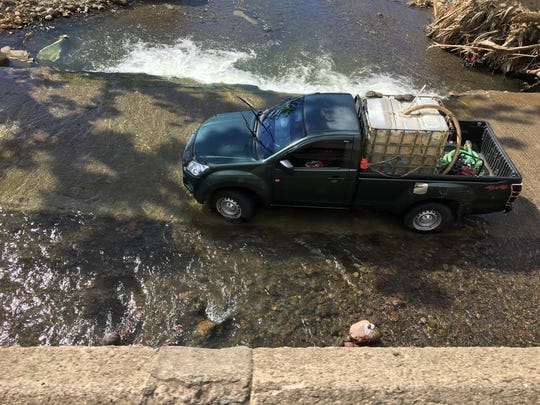 A truck in Dominica pumps water from the river so it can be taken to nearby villages which have had trouble accessing clean drinking water since Hurricane Maria.
