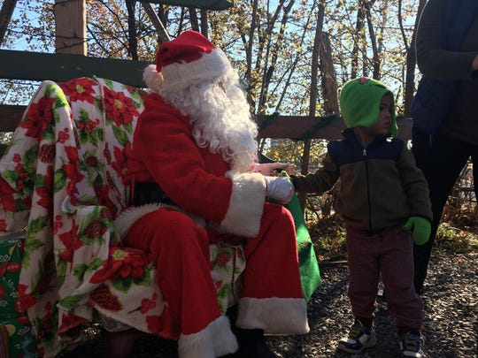 Noah Duplessis, 3, meets Santa on Friday. He asked him where the reindeer were today.