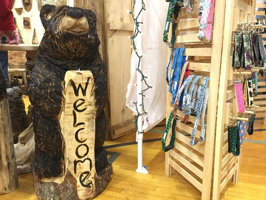 A carved bear holding a welcome sign sits outside of