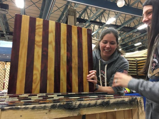 Kate Thomas of Veteran Made Woodworks LLC puts an American