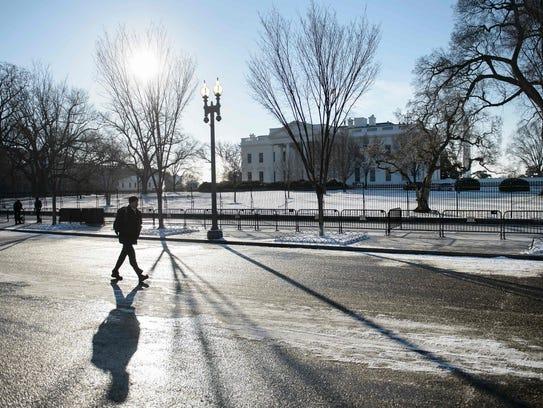 A man walks along Pennsylvania Avenue past the White