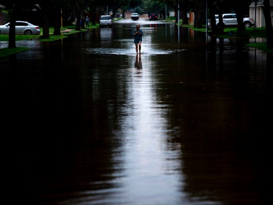 A woman walks down a flooded road during the aftermath