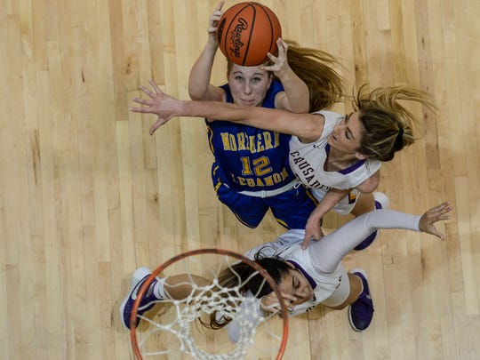 Northern's Lebanon's Amber Kintzer grabs a rebound against Lancaster Catholic's Caroline Scarff (right) and Corina Rivera (bottom).