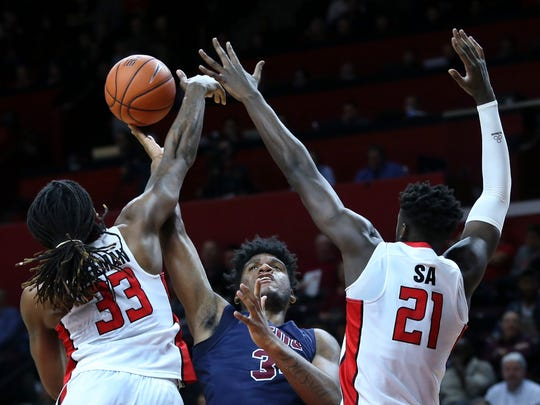Fairleigh Dickinson forward Mike Holloway (34) goes up for a shot between Rutgers defenders Deshawn Freeman (33) and Candido Sa, (21) of Portugal, during the second half of an NCAA college basketball game, Wednesday, Dec. 14, 2016, in Piscataway, N.J. (AP Photo/Mel Evans)