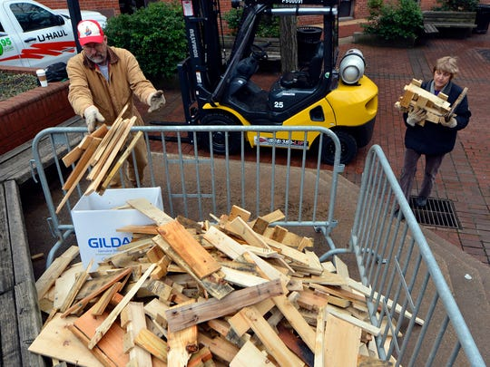 Volunteers Ed and Suzann Gallagher help unload firewood