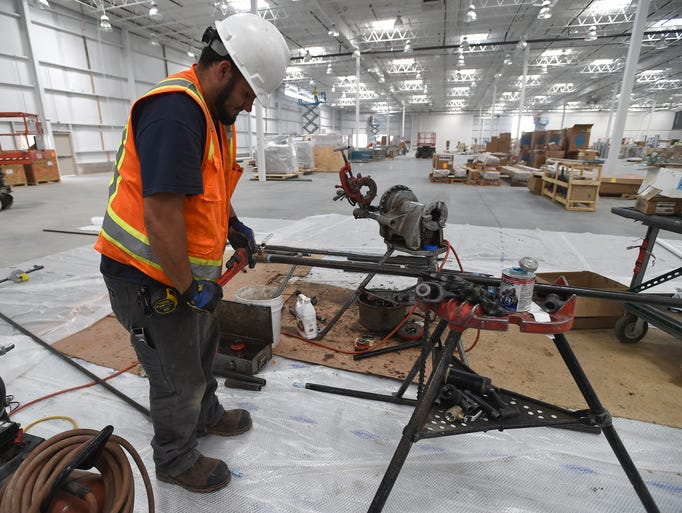 Evin Brewer, a plumber apprentie with Corporate Plumbing, based in Fort Collins, prepares water pipe as work continues at the Costco Warehouse in Timnath  Wednesday Aug. 13, 2014. Opening is set for early October.