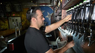 Wesley Keegan, owner Tailgate Beer Brewery, pours beer in the taproom at the Charlotte Pike location.