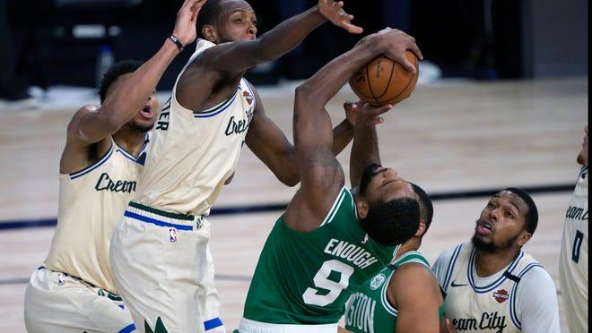 Milwaukee Bucks' Khris Middleton defends against Boston Celtics' Brad Wanamaker (9) during the first half of an NBA basketball game Friday, July 31, 2020, in Lake Buena Vista, Fla.