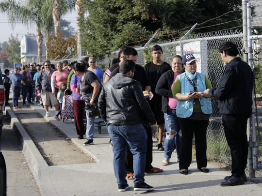 Visalia residents wait in line to pick-up their food