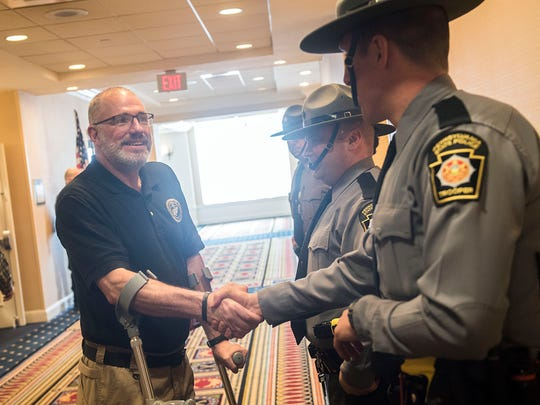 Bob Bemis, left, shakes the hand of a Pennsylvania State Police Trooper prior to receiving his customized Rogue wheelchair, Monday, February 13, 2017. Bemis, who retired from the PSP in January, was disabled when he was hit by a car on duty, in March 2015.