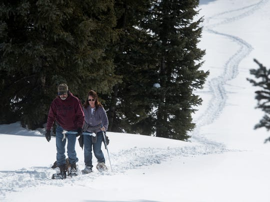 Rusty and Teresa Hector, of Pagosa Springs, Colo., snowshoe on Friday at Andrews Lake near Molas Pass in Colorado.