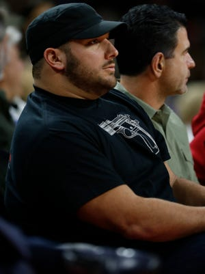 Detroit Lions center Dominic Raiola sits courtside during the Detroit Pistons' 128-118 win over the Orlando Magic on Jan. 21, 2015, in Auburn Hills.