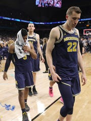 Zavier Simpson, left, and Duncan Robinson leave the floor after the loss.
