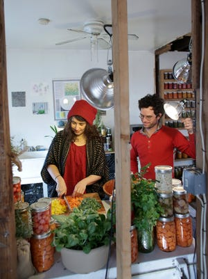 Artists Kate Daughdrill, left, and Patrick Costello prepare jars of her vegetables at her home in Detroit on Wednesday. The jars will be displayed in a prism-like installation as a part of the Art X Detroit festival.