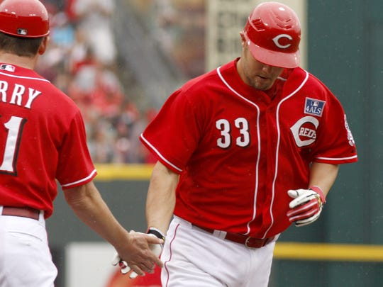 The Cincinnati Reds' Micah Owings, right, is congratulated by third base coach Mark Berry after Owings hit a solo home run off St. Louis Cardinals pitcher Brad Thompson in the second inning July 4, 2009, in Cincinnati.