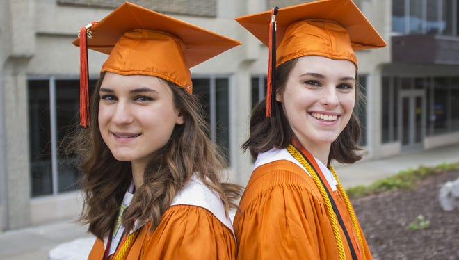 Twins Mary (left) and Sophia Vitello of DeWitt graduate Sunday from Great Lakes Cyber Academy with Mary as valedictorian and Sophia as salutatorian. Commencement was at Lansing Community College's Dart Auditorium.